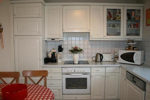 Weiße Küche in L-Form mit Hängeschränken und Elektrogeräten in ... | {Küchen l form mit elektrogeräten 14}